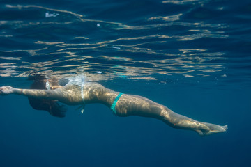 A girl swimmer getting rest near water surface in blue sea