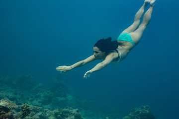 A brunette girl diving into blue sea water. Underwater photography of sport activity