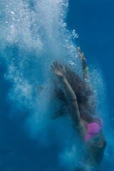 Drowning girl in pink bikini. A swimmer after jump underwater surrounded with air bubbles. Image on blue aquatic marine background