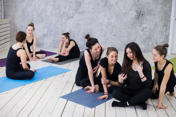 Making selfie. Group of girls in fitness class at the break looking at cell phone, happy and smiling, show funny face. Woman friendship, healthy modern life of young people concept.