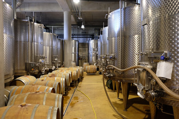 Interior of a modern underground winery with aluminium tanks and wine barrels