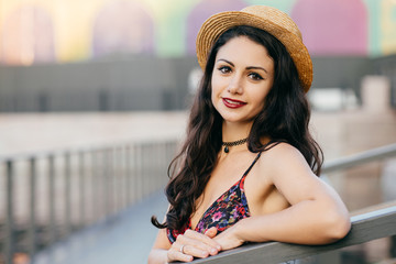 Lovely woman with dark long hair, appealing appearance wearing summer hat and dress having excursion in big city posing at bridge. Young female traveler walking on street having delightful look
