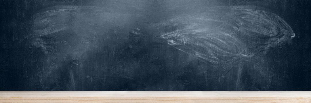 School blackboard with wooden table background