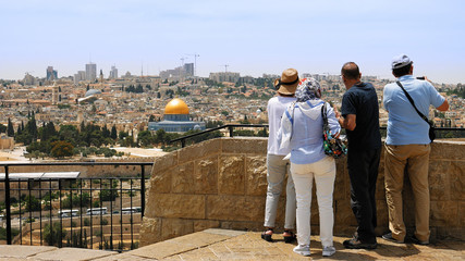 The guide shows the Jerusalem Old City view to the tourists and pilgrims. Mount of Olives is a famous Holy Land place and it has a fantastic view to the Old Jerusalem