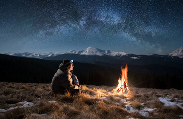 Male tourist have a rest in the mountains at night. Man with a headlamp sitting near campfire under beautiful night sky full of stars and milky way, and enjoying night scene Wall mural