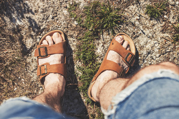 Top view of male legs in brown leather sandals and blue jean shorts, standing on a rocky trail