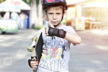 Boy with skateboard showing thumbs up