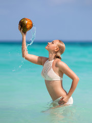 Girl posing in the sea with open coconut