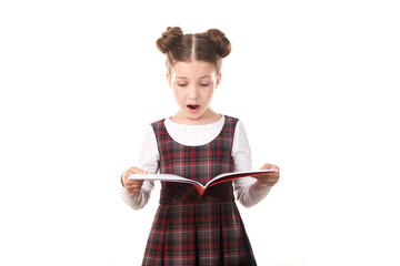 Scared elementary school girl holding open book against white background