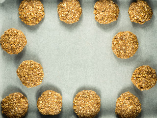 Table with raw oat cookies over baking paper