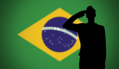 Silhouette of a soldier saluting against the brazil flag