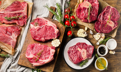 Raw beef meat on a dark wooden board. Wall mural