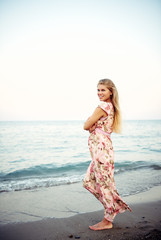 Happy pregnant female in stylish dress standing barefoot on seashore. Pregnancy, healthy lifestyle and motherhood concept.
