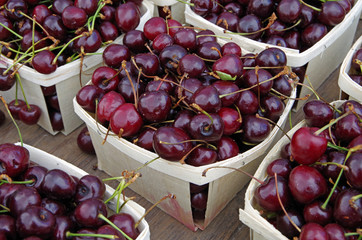 Dark red cherries with stems displayed in wooden containers closeup