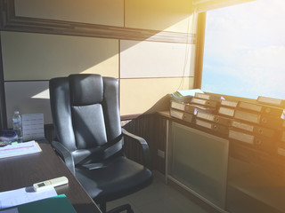 Black leather armchair in office room with morning sun light.
