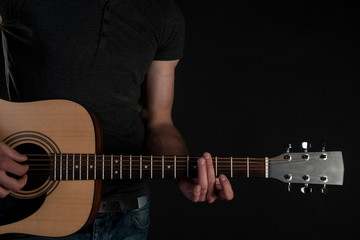 Acoustic guitar in male hands, on a black isolated background. Horizontal frame