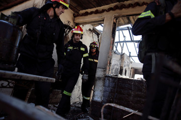 Firefighters exit a burnt-out house following a wildfire in the area of Kalyvia, near Athens