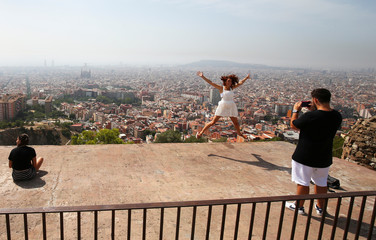 A tourist leaps in the air for her photograph with the skyline of Barcelona in the background