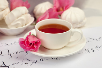 Mother's day Valentine concept, cup of tea, pink flowers, sweets, notes