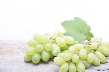 Green grapes on the wood table and white background