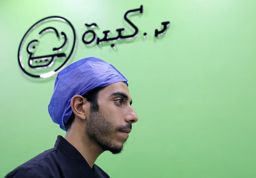 """An employee dressed as a doctor walks beneath a sign reading in Arabic """"Doctor Liver"""" at the operating room-themed fast food restaurant in Damanhour"""