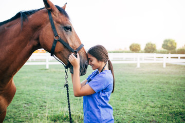 Vet petting a horse outdoors at ranch.  Wall mural