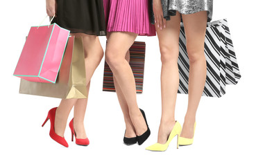 Young women with beautiful legs holding shopping bags on white background