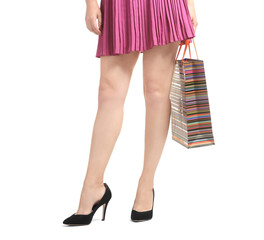 Young woman with beautiful legs holding shopping bag on white background