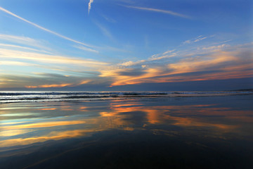 Sky mirrored by wet beach during sunset