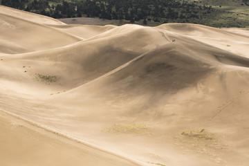 Hikers walking on top of giant sand dunes