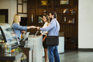 A nice looking couple takes their room key from receptionist at the reception.