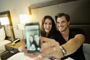 A young couple sits side by side on a bed in a Dallas hotel room takes a selfie.