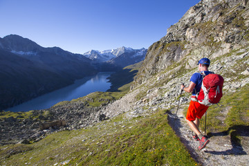 A solo male hiker enjoying the view over Lac des Dix in Val d'Hérémence, in the Swiss Alps.