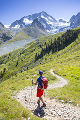 A colorful dressed male hiker is descending curved mountain trail in a green summer landscape with glaciers in the background.