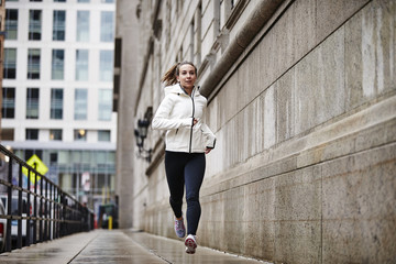 A female runner running through the city