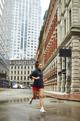 A young asian girls runs through the wet city streets of Boston.