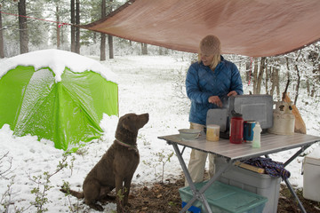 A woman and her dog cooking under snowy tarp, Dolores, Colorado.