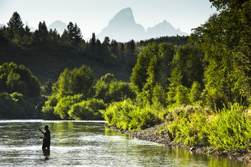 A fly fisherman in a river with mountains in the background.
