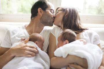 Mother And Father Kissing While Holding Their Twin Babies