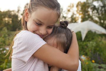 Sisters Hugging In Garden, British Columbia, Canada