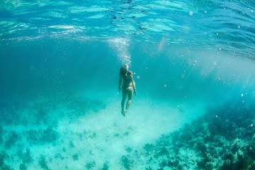 Girl (20-30 years old) in bikini swims under the surface in cristal blue water in the coast off to Trinidad, Cuba