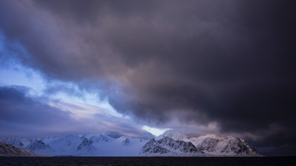 Dramatic sky against snowcapped mountains