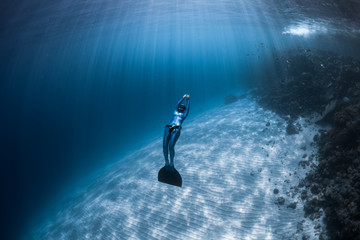 Wall Mural - Woman freediver glides over sandy bottom of a crystal clear tropical sea