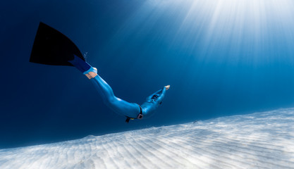 Wall Mural - Woman freediver glides over sandy sea bottom