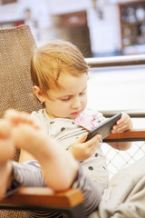 Social Media addiction. Little baby girl  holding smart phone (psychological problems, media mania, education)