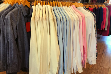 Colourful textile shirts hanging on a rack in a row in the store.
