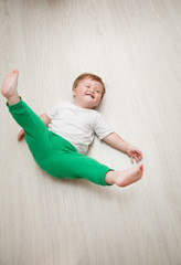 happy baby boy in white t-shirt and green pants lying on her back on a wooden floor