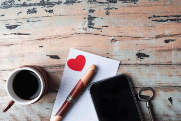 Cup and phone on the old wooden background. Top view, trend concept.