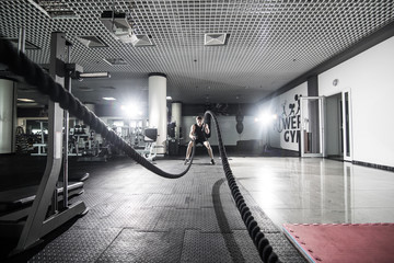 Athletic man doing some cross-training exercises with a rope in gym. Crossfit
