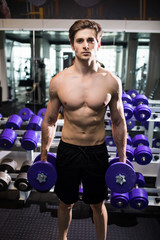 very power athletic guy , execute exercise with dumbbells, in gym hall